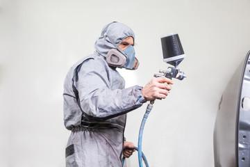 Car body painter spraying paint on bodywork parts