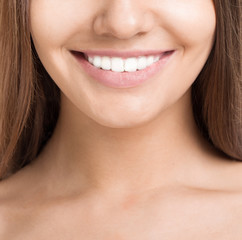 Portrait of beautiful smiling young woman with perfect skin and teeth. Closed up