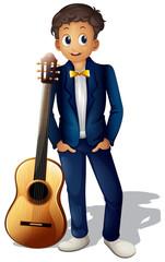 A boy standing beside the guitar