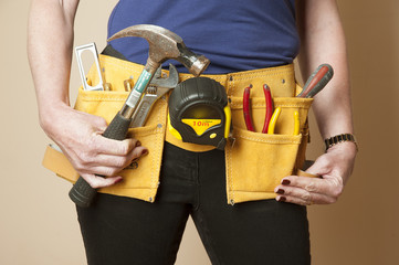 Female worker wearing a toolbelt work apron