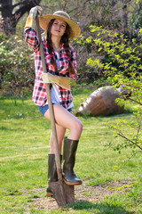 Beautiful girl with hay hat posing with a shovel