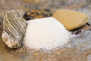 Pile of Fresh Coarse Salt in front of Rocks