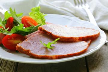 Baked sliced ham served with green salad