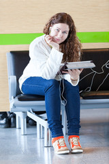 Young woman with electronic devices sitting on chair