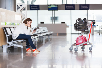Tired woman waiting flight in airport lounge with luggage cart
