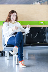 Happy woman charging her electronic devices in place to charge