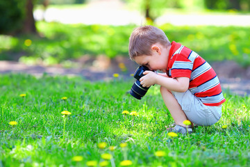 cute kid boy photographing flowers