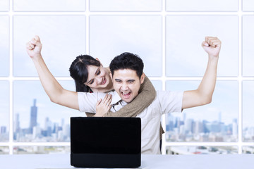 Happy couple with laptop in office