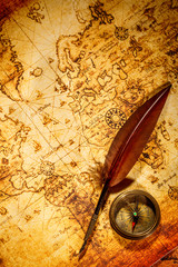 Wall Mural - Vintage compass and goose quill pen lying on an old map.