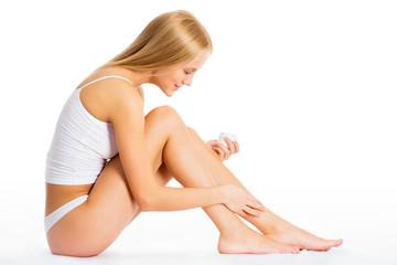 Woman applying moisturizer on leg