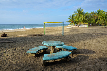 Tropical beach with football goals on the sand and a round table with benches in foreground, Costa Rica