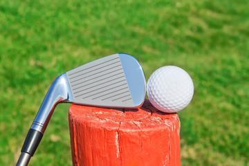 Golf stick upside down on a wooden ball pedestal on the grass. C