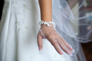 Bride's hands with manicure in white  lace gloves