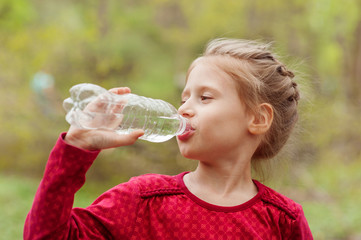 Girl drinks water from a bottle in a park