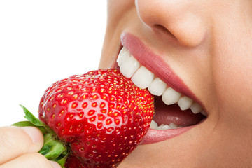 Extreme close up of teeth biting strawberry.