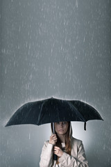 Young woman under an umbrella during rainfall