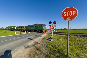 railroad crossing with stop sign and train passing