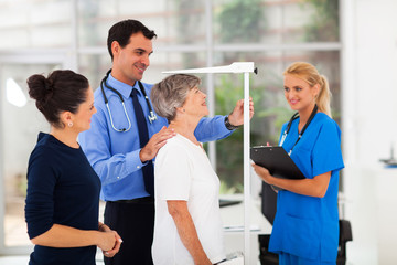 general practitioner measuring senior patient's height