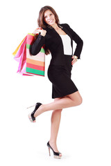 Happy young woman goes and carries bags with purchases