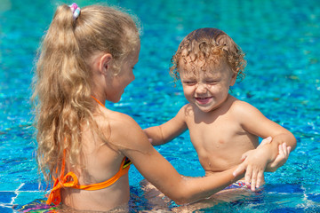 little girl and little boy playing in the swimming  pool