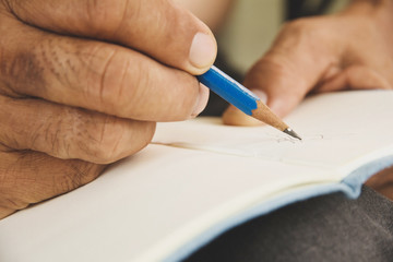 man writing on sketchbook