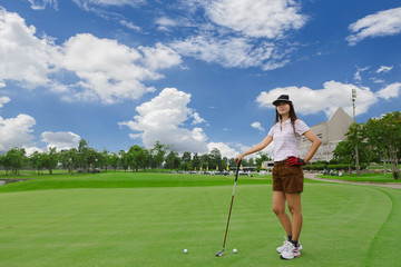 Young woman playing golf on a green golf course