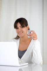 Young woman with a water glass in front of laptop