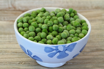 Bowl of frozen green peas, close up