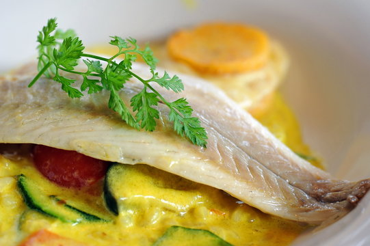 Sea bass fish fillet with parsley and curry sauce
