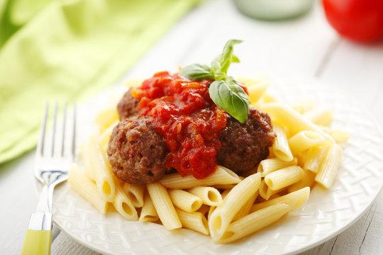 Italian meatballs with penne pasta in tomato sauce
