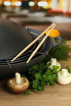 Black wok pan and vegetables on kitchen wooden table, close up