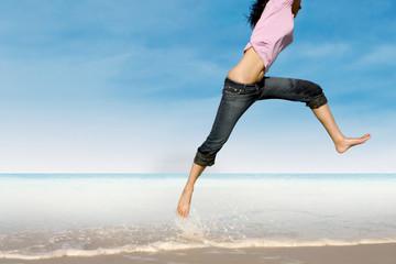 Close-up of woman jumping at beach