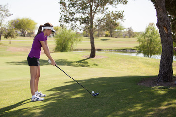 Latin golfer concentrating on the ball and ready to swing