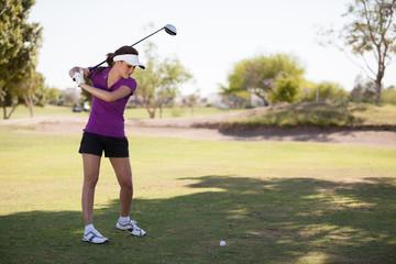 Cute female golfer swinging at a golf ball in a sunny day