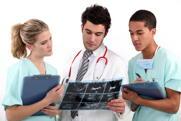 A doctor and his assistants checking a radiography.