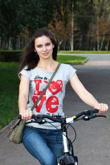 Девушка катается на велосипеде по парк