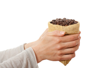 A small bag of coffee beans in female hands, isolated on white