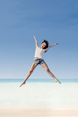 Girl jumping under blue sky