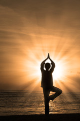 Silhouette of woman doing yoga at beach