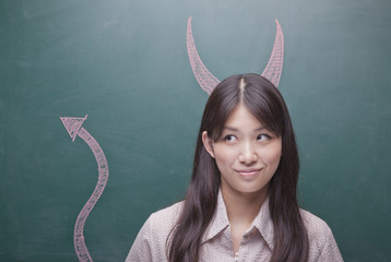 Young woman with devil horns and tail on blackboard
