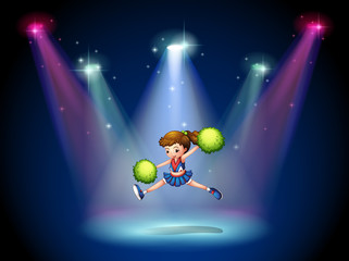 A cheerleader jumping on the stage with spotlights