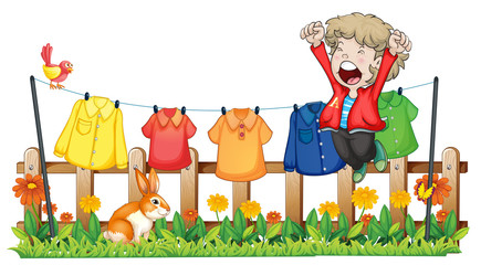 A young boy jumping near the hanging clothes