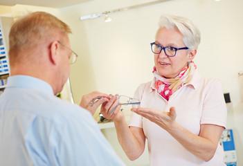 Customer buying glasses at optician