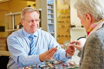Optician giving consultation to senior woman