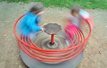 Dua bambini su una giostra girello che gira veloce