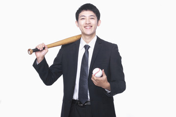 Businessman smiling with bat and baseball