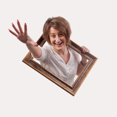 Funny beautiful woman coming out from a empty frame