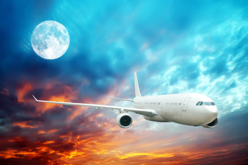 A plane flying high in the nighttime sky