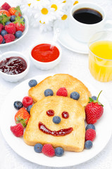 Breakfast with a smiling toast, fresh berries, jams, juice