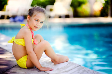 Pretty little girl playing in outdoor swimming pool and have a f